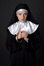 Portrait of young beautiful woman nun praying with rosary over g grey background Stock Images