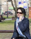 A young woman with a joyful mood communicates on a smartphone in a spring park