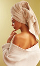 Portrait of young beautiful woman wearing bathrobe and towel on her head in bedroom relaxing after shower bathing Royalty Free Stock Photography
