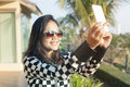 Portrait of young beautiful woman wearing sun glasses take a pho photo selfie by mobile phone use for modern digital life and Stock Photo