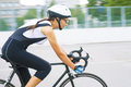 Portrait of young beauty caucasian professional cyclist on the m single female athlete riding bicycle a race track horizontal Stock Photo