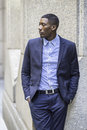 Portrait of young black businessman a is standing outside and taking a break Royalty Free Stock Photos