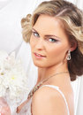 Portrait young blond bride posing in a white dress of and beautiful with flower bouquet the image is taken on silk background Royalty Free Stock Photo