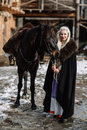 Portrait of a young blond woman in a black cloak with a horse. Royalty Free Stock Photo
