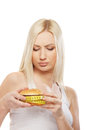 Portrait of a young blond woman holding a burger Royalty Free Stock Images
