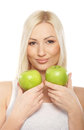 Portrait of a young blond woman holding two apples Stock Photo