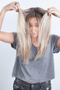 Portrait of a young blond woman playing with her hair Royalty Free Stock Photo