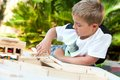 Portrait young boy building structure wooden blocks outdoors Royalty Free Stock Photo