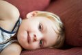 Portrait of young boy lying on sofa at home looking camera smiling Royalty Free Stock Photography