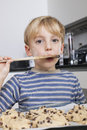 Portrait of young boy tasting spatula mix with cookie batter Royalty Free Stock Photos