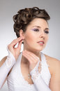 Portrait of a young brunette bride in makeup and happy caucasian beautiful the girl is putting on an earring the image is taken on Stock Photography