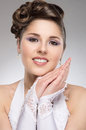 Portrait of a young brunette bride in makeup and happy caucasian beautiful the image is taken on grey background Royalty Free Stock Photo