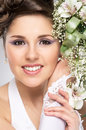 Portrait of a young brunette bride in a white dress beautiful and emotional with beautiful flowers the image is taken on grey Royalty Free Stock Photos