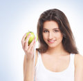 Portrait of a young brunette holding a fresh apple Royalty Free Stock Images