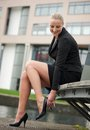 Portrait of a young business woman adjust her shoes outdoors Stock Photos