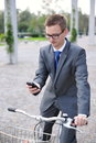 Portrait of young businessman on a bike using mobile phone outdoors Royalty Free Stock Image