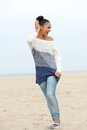 Portrait of a young carefree woman walking on the beach full length Royalty Free Stock Image