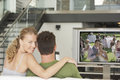 Portrait of young caucasian woman with man watching movie on television in living room women men Stock Photos
