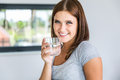 Portrait of young cheerful woman with glass of mineral water Royalty Free Stock Photo