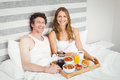 Portrait of young couple having breakfast on bed smiling at home Stock Photography