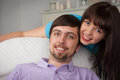 Portrait of young couple at home pretty women hugging her boyfriend on the couch in the living room Stock Photography