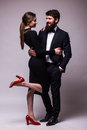 Portrait of young couple in love posing dressed in classic clothes on grey backround man with beard in suit woman in black dress Stock Photos