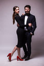 Portrait of young couple in love posing dressed in classic clothes on grey backround. Man with beard in Suit, Woman in black Dress Royalty Free Stock Photo