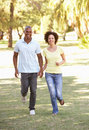 Portrait Of Young Couple Running Through Park Stock Photo