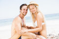 Portrait of young couple sitting together on the beach a sunny day Royalty Free Stock Photo