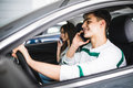 Portrait of a young couple speal phone and driving together, as seen through the windshield