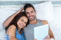 Portrait of young couple with tablet while lying on bed Royalty Free Stock Photo