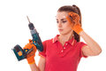 Portrait of young cute brunette builder girl makes renovation with drill in hands isolated on white background Royalty Free Stock Photo