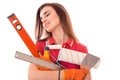 Portrait of young cute brunette builder girl makes renovation with tools in hands isolated on white background Royalty Free Stock Photo