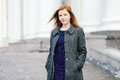 Portrait of young cute redhead woman in blue dress and grey coat  on the porch at winter outdoors Royalty Free Stock Photo