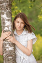 Portrait of young dark haired woman embracing birch tree attractive wearing white chemise at summer green park Stock Images
