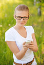 Portrait of young fair haired woman looking at mobile phone beautiful wearing white dress telephone summer green park Stock Images