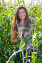Portrait of young farm girl in corn field at green background Stock Photos