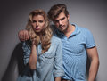 Portrait of a young fashion couple standing embraced and looking at the camera in studio Stock Photos