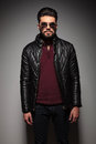 Portrait of a young fashion man with long beard wearing leather jacket and sunglasses Royalty Free Stock Photography