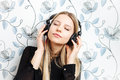 Portrait of young fashionable blonde woman enjoying music in big dj headphones indoors Royalty Free Stock Image