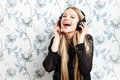 Portrait of young fashionable blonde woman enjoying music in big dj headphones indoors Stock Photos