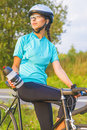 Portrait of young female caucasian cyclist athlete on bicycle ha having a water break vertical image Royalty Free Stock Photos
