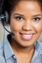 Portrait of young female customer service agent smiling representative wearing headset in office Royalty Free Stock Image