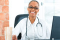 Portrait of young female doctor in clinic black sitting at a window she has a stethoscope Royalty Free Stock Photo