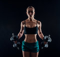 Portrait of a young fitness woman in sportswear doing workout with dumbbells on black background. Tanned sexy athletic girl. Royalty Free Stock Photo