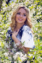 Portrait of a young girl blondes with make up in the cherry sakura pink white in white skirt and blue top Royalty Free Stock Images