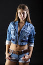Portrait young girl in a blue jeans jacket and shorts in dark st Royalty Free Stock Photo