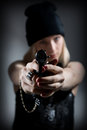 Portrait of a young girl with a gun hooligan in dark cap targets the enemy sharpshooter pistol Royalty Free Stock Photography