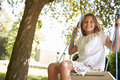 Portrait Of Young Girl Playing On Tree Swing Royalty Free Stock Photo