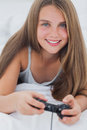 Portrait of a young girl playing video games while she is lying on her bed Stock Image